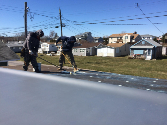 The application of the adhesive to the fiberboard and to the TPO roof membrane
